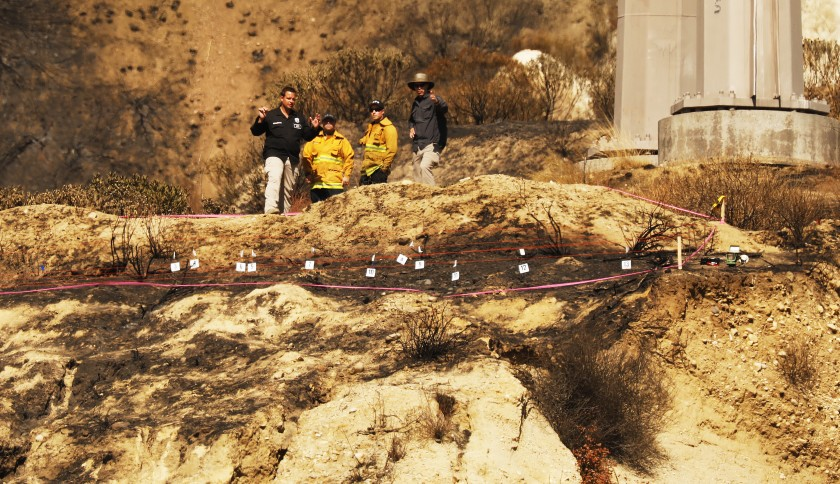 Fire inspectors comb the scene in the foothills behind the homes in Sylmar under a Southern California Edison transmission tower and line as investigators try to determine the cause of the deadly Saddleridge Fire in this undated photo. (Credit: Al Seib/ Los Angeles Times)
