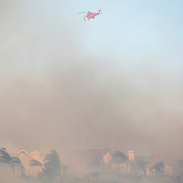 A firefighting helicopter works the Saddleridge Fire as smoke blows over homes on Oct. 11, 2019 near Porter Ranch. (Credit: Mario Tama/Getty Images)