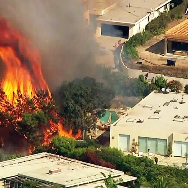 A brush fire burns near a home in Pacific Palisades on Oct. 21, 2019. (Credit: KTLA)