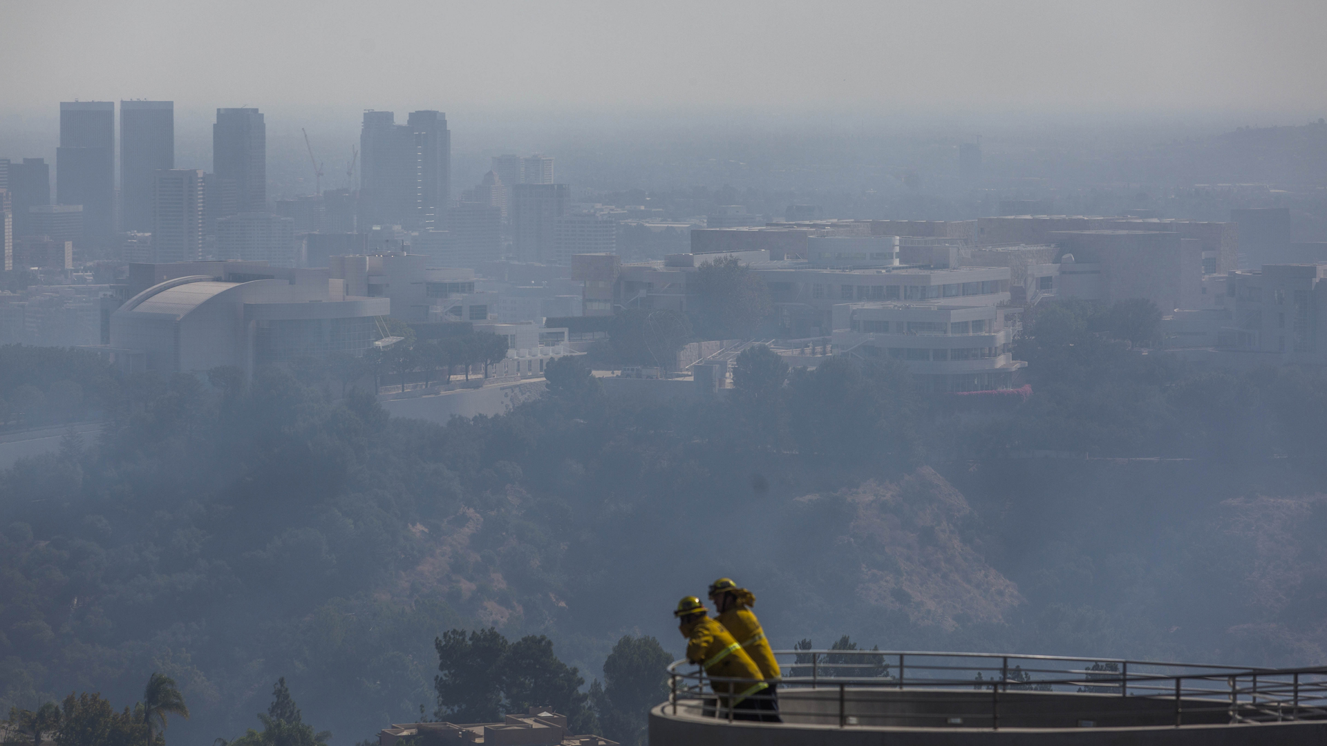 Firefighters stand on a balcony overlooking the Getty Center as the Getty Fire burns in Brentwood on Oct. 28, 2019. (Credit: Apu Gomes / AFP / Getty Images)
