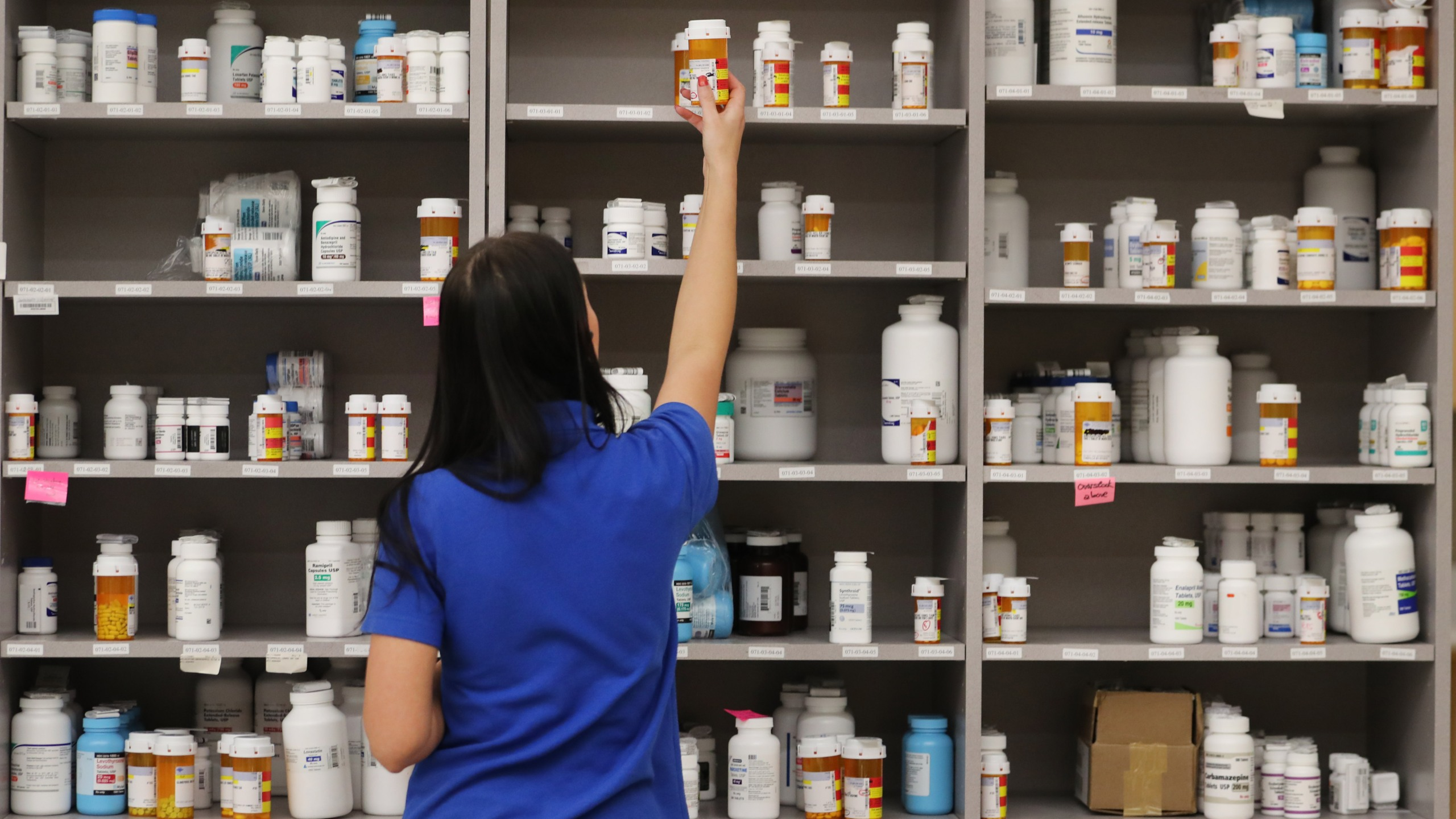 A pharmacy technician grabs a bottle of drugs off a shelve at the central pharmacy of Intermountain Heathcare on Sept. 10, 2018, in Midvale, Utah. (Credit: George Frey/Getty Images)
