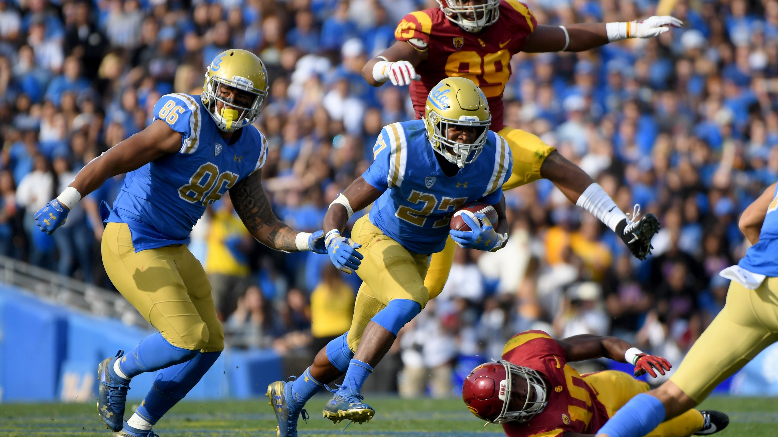 Joshua Kelley of the UCLA Bruins runs with Devin Asiasi during a match at the Rose Bowl on Nov. 17, 2018 in Pasadena. (Credit: Harry How/Getty Images)