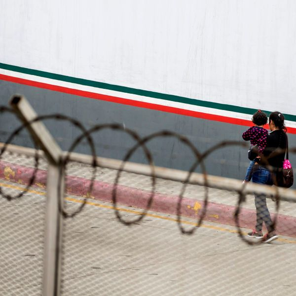 A Central American migrant and her children walk outside El Chaparral port of entry, in Tijuana, Mexico, on July 17, 2019. (Credit: Omar Martínez / AFP / Getty Images)