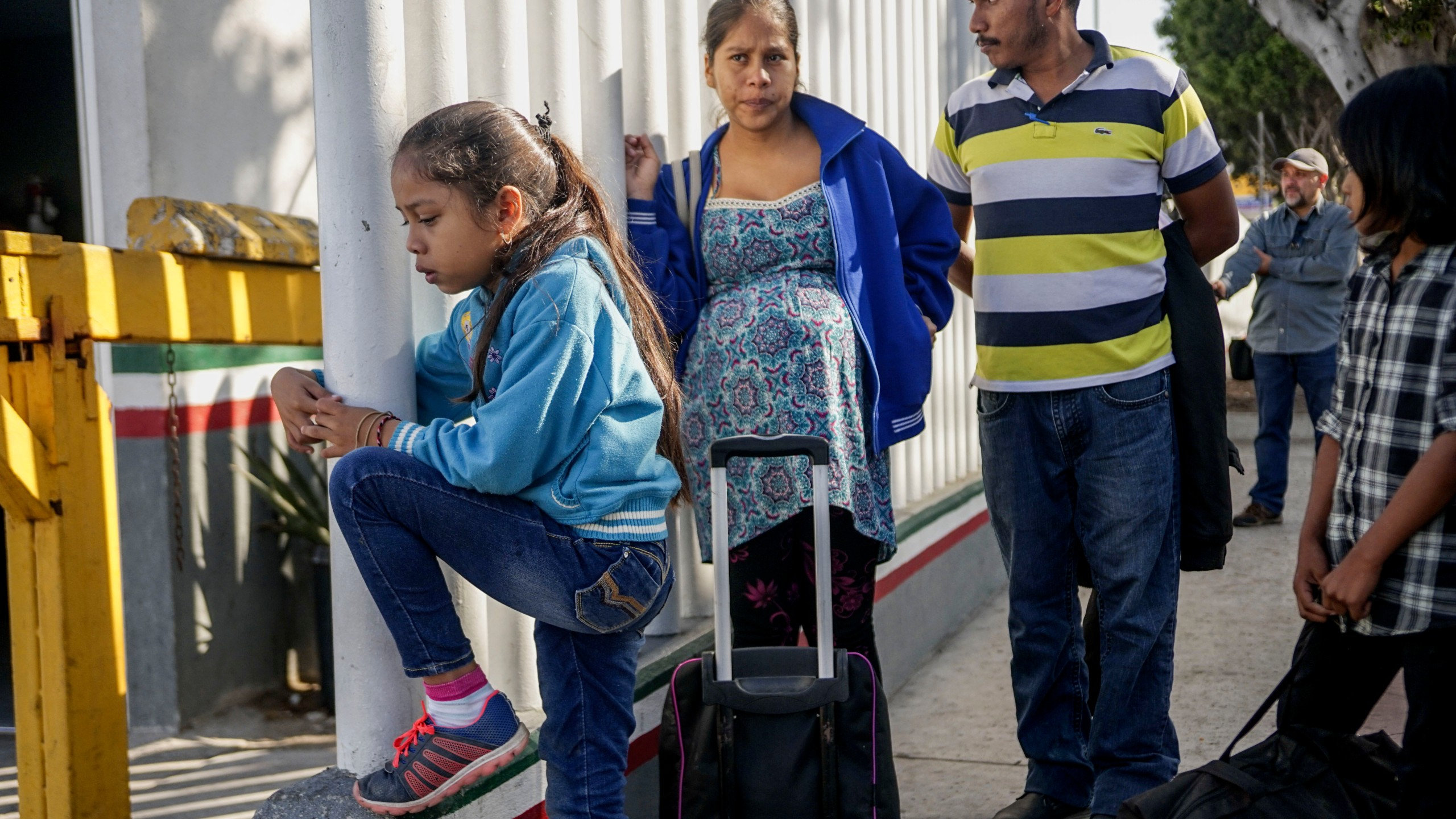 Migrants from Honduras wait in line at the Mexico-U.S. border crossing in Tijuana, Mexico on Sept. 12, 2019. (Credit: SANDY HUFFAKER/AFP/Getty Images)