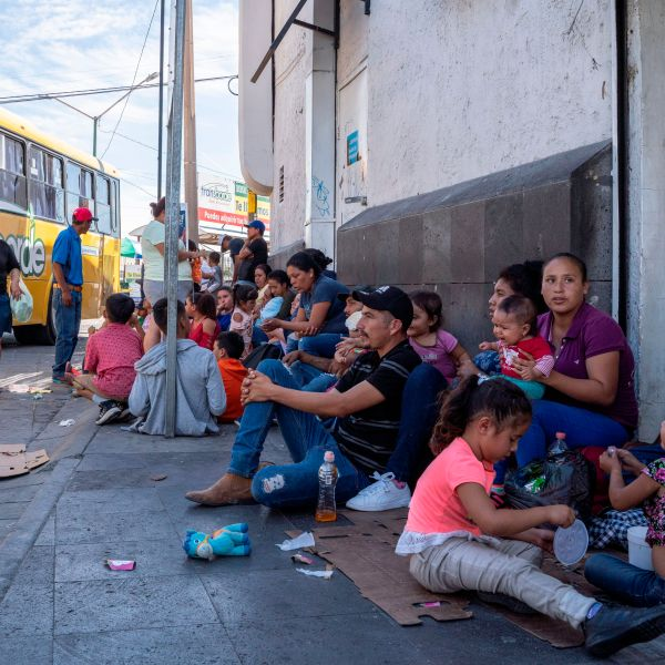 Migrants, mostly from Mexico, sit on the ground as they wait near the Paso del Norte Bridge at the Mexico-U.S. border in Ciudad Juarez, Mexico, on Sept. 12, 2019. (Credit: Paul Ratje / AFP / Getty Images)