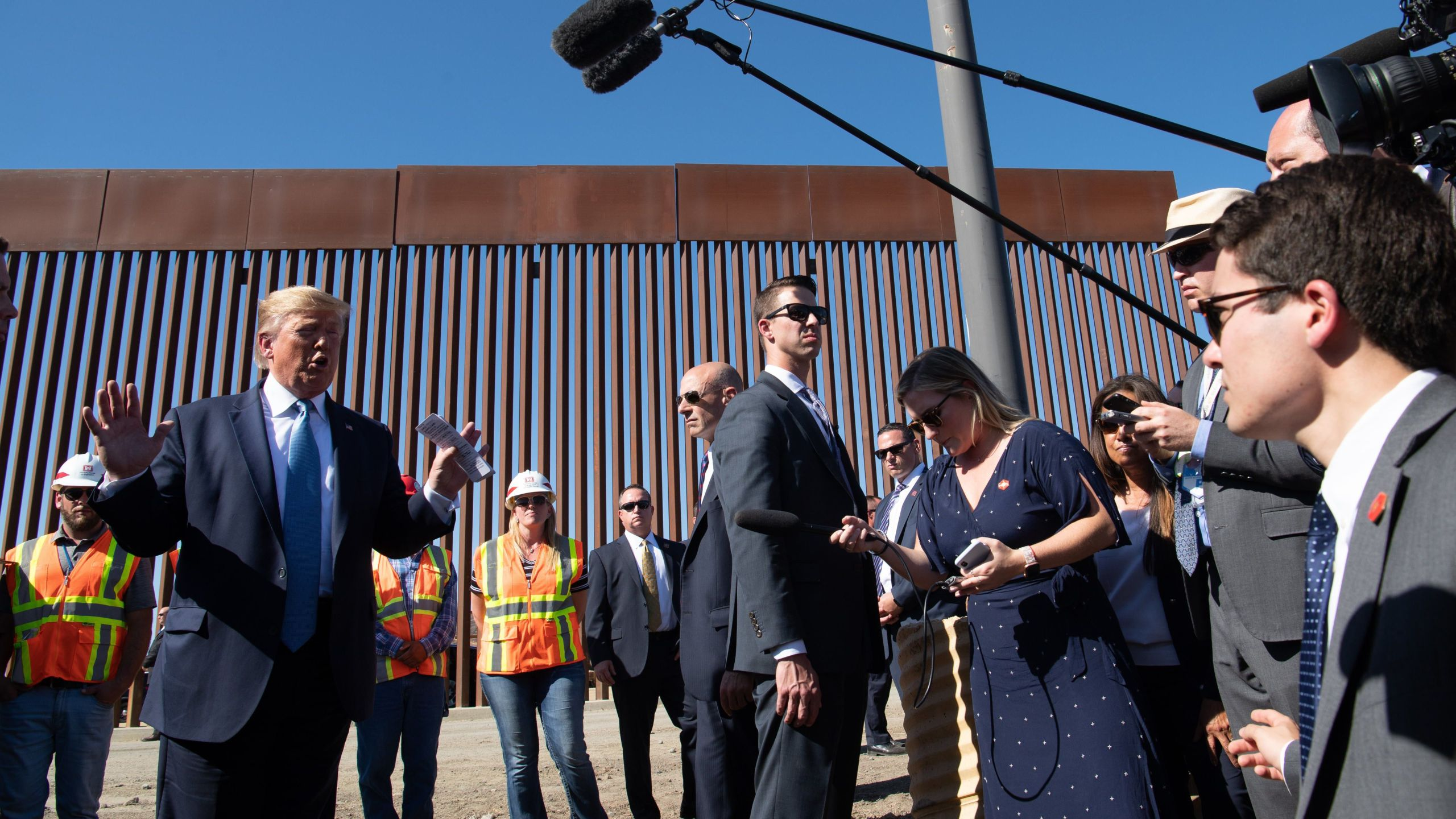 Donald Trump, left, speaks to the media during a visit the U.S.-Mexico border fence in Otay Mesa on Sept. 18, 2019. (Credit: NICHOLAS KAMM/AFP/Getty Images)