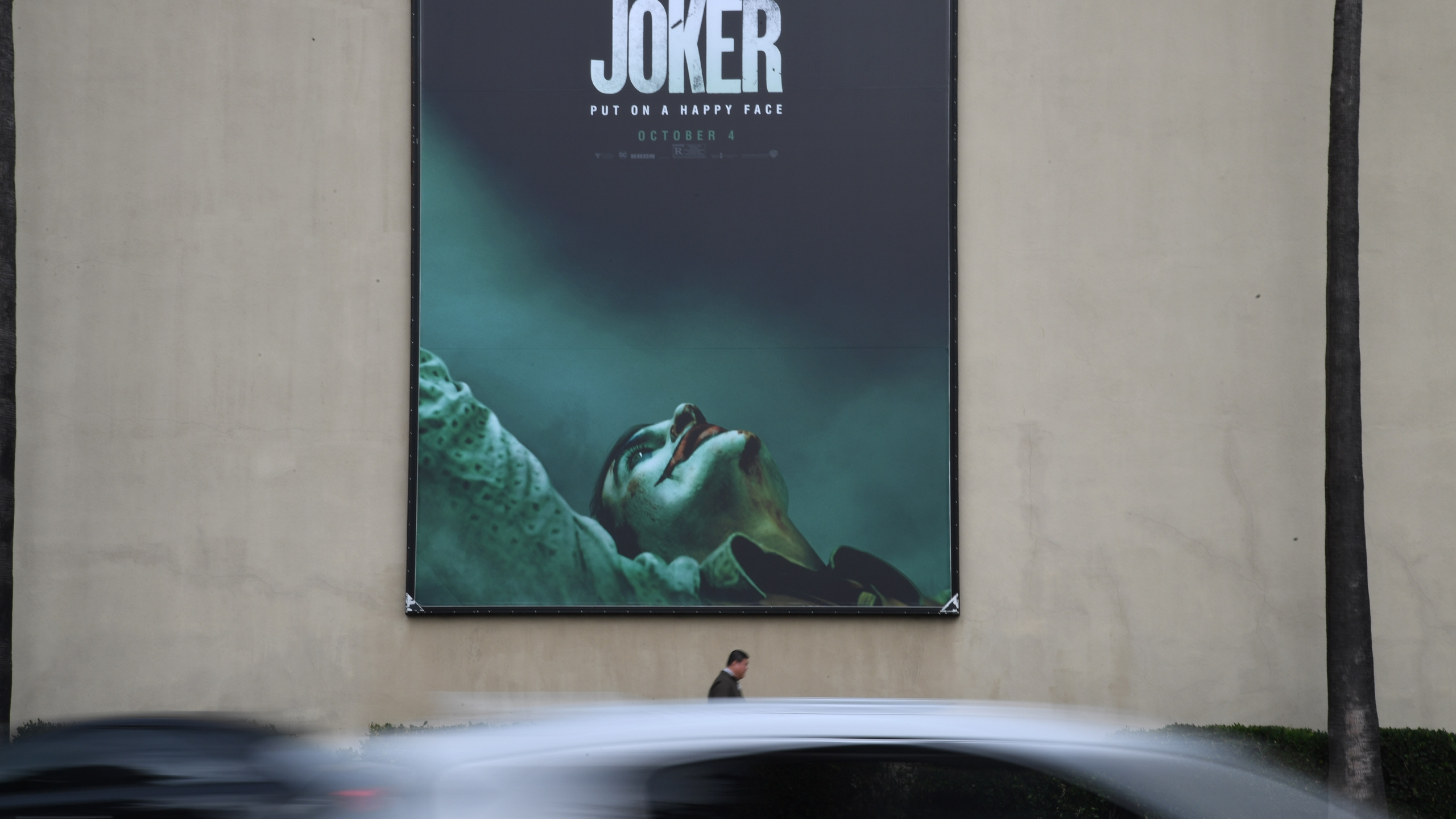 """A poster for the upcoming film """"The Joker"""" is seen outside Warner Brothers Studios in Burbank, Calif., Sept. 27, 2019. (Credit: ROBYN BECK/AFP/Getty Images)"""