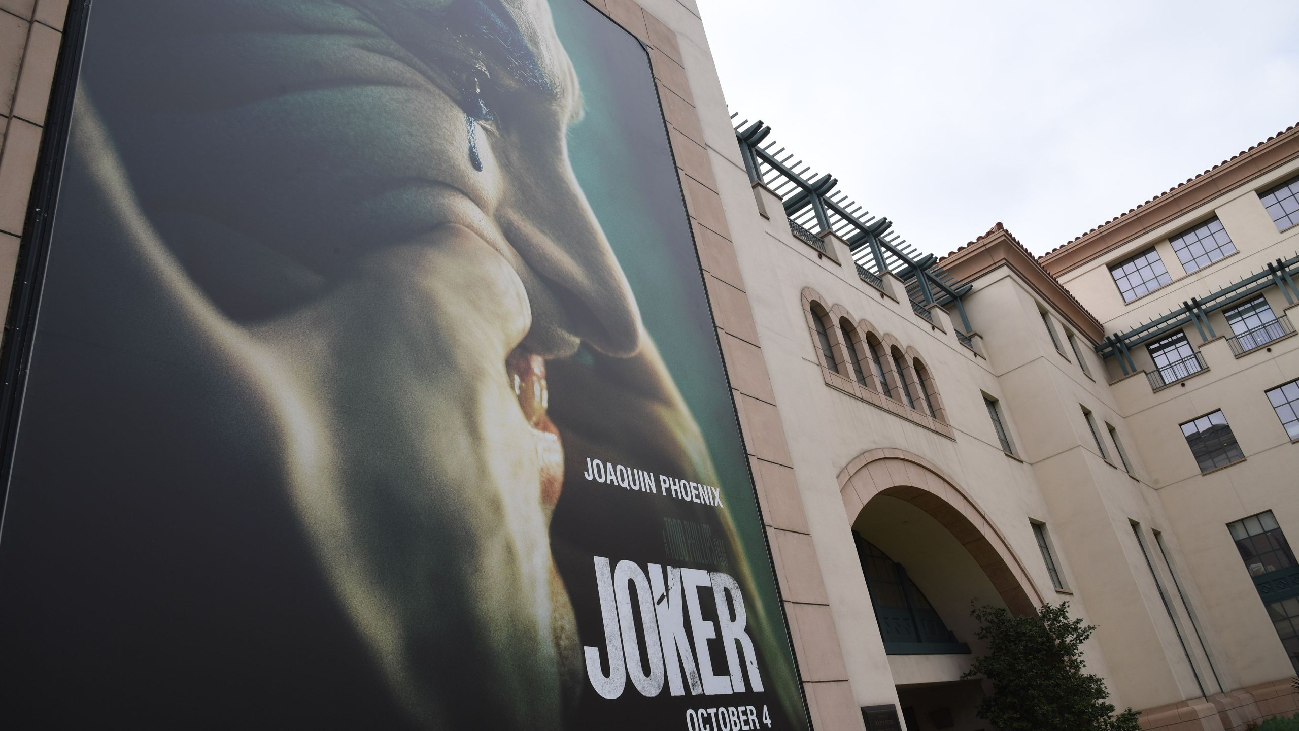 """A poster for the upcoming film """"The Joker"""" is seen outside Warner Brothers Studios in Burbank, California, Sept. 27, 2019. (Credit: ROBYN BECK/AFP/Getty Images)"""