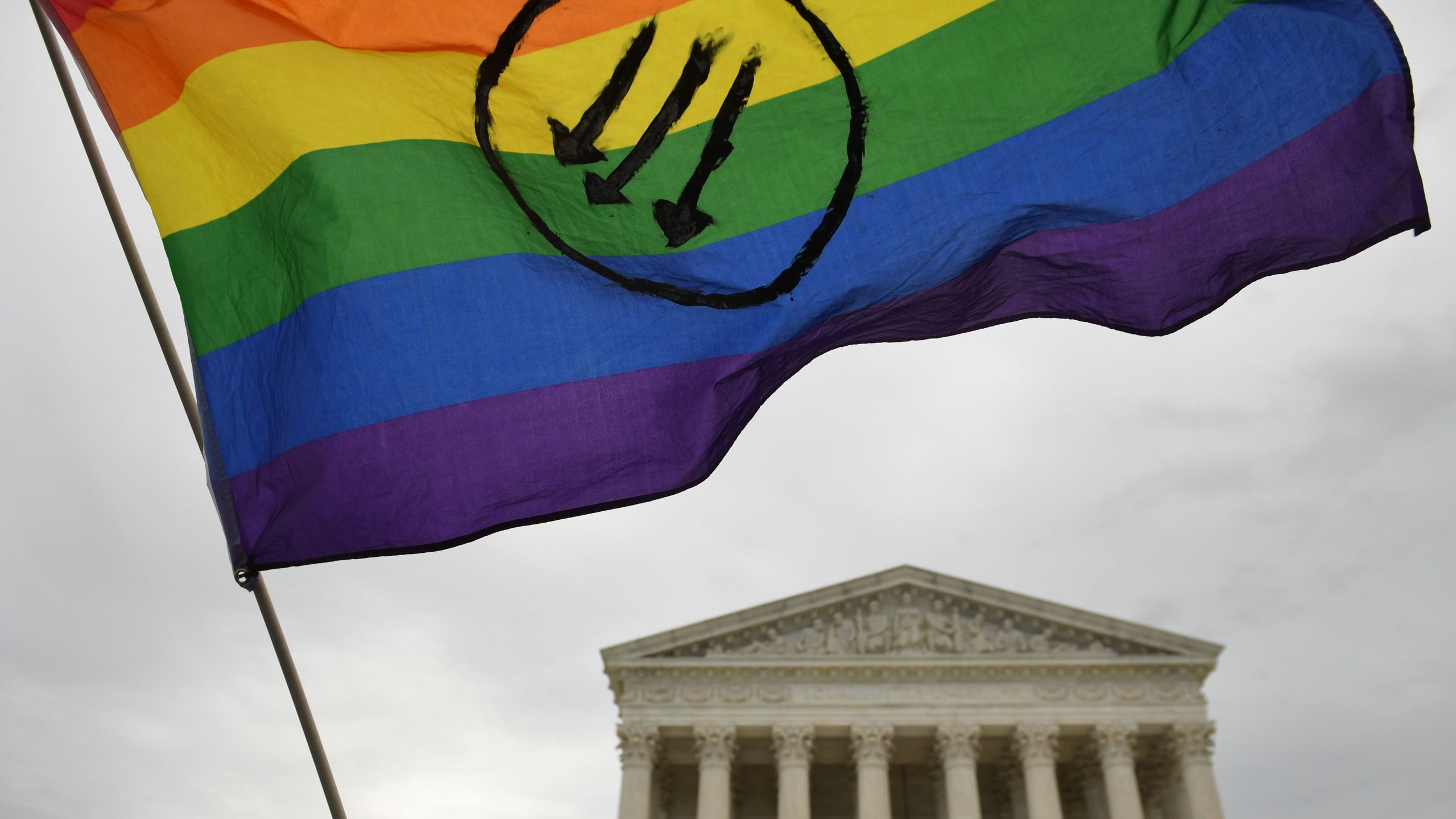 Demonstrators hold up a rainbow flag at an LGBT rights rally outside the U.S. Supreme Court in Washington, D.C., on Oct. 8, 2019, as the court holds oral arguments in cases dealing with workplace discrimination based on sexual orientation. (Credit: SAUL LOEB/AFP via Getty Images)