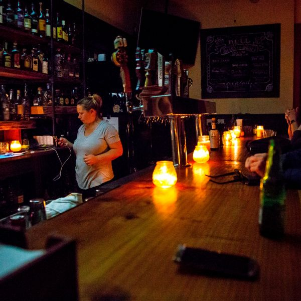 Restaurant owner Emily Schiffman checks her phone behind a candle-lit bar at Reel and Brand in Sonoma on Oct. 9, 2019, during a planned power outage by Pacific Gas & Electric. (Credit: Brittany Hosea-Small / AFP / Getty Images)