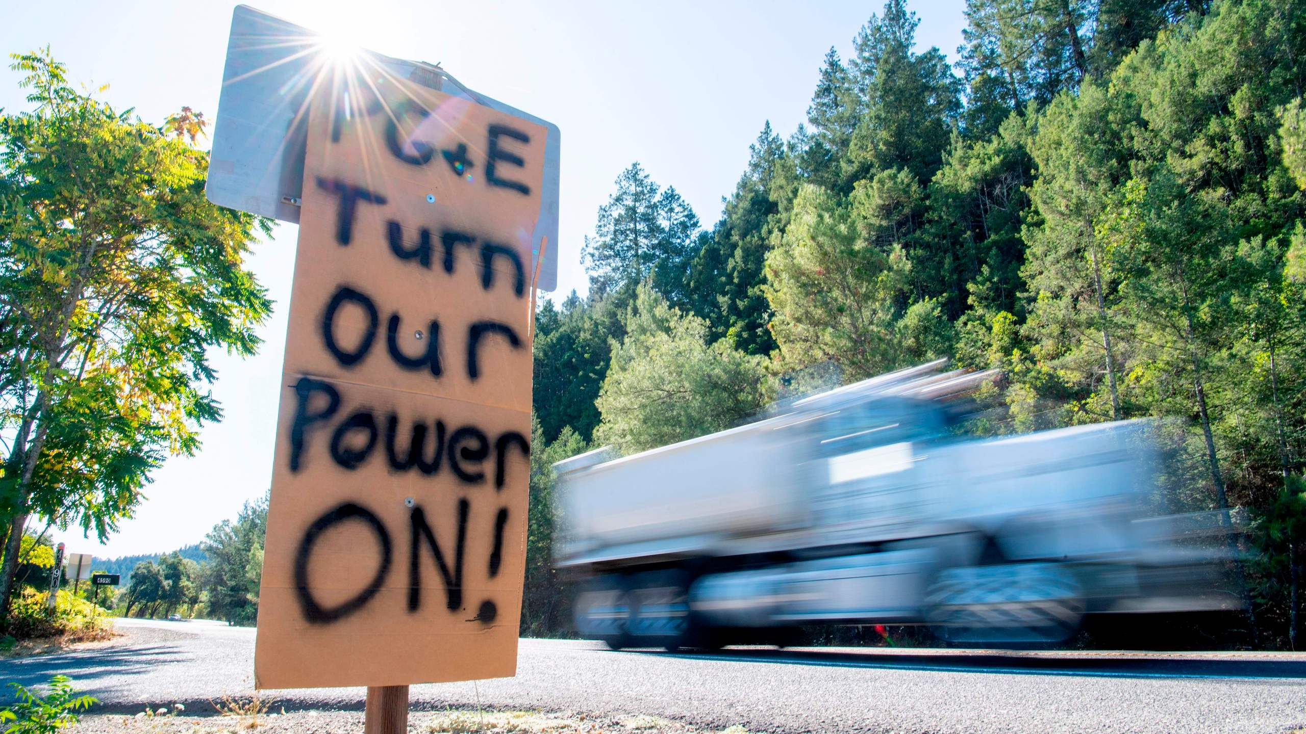 A sign calling for PG&E to turn the power back on is seen on the side of the road during a blackout in Calistoga on Oct. 10, 2019. (Credit: Josh Edelson / AFP via Getty Images)
