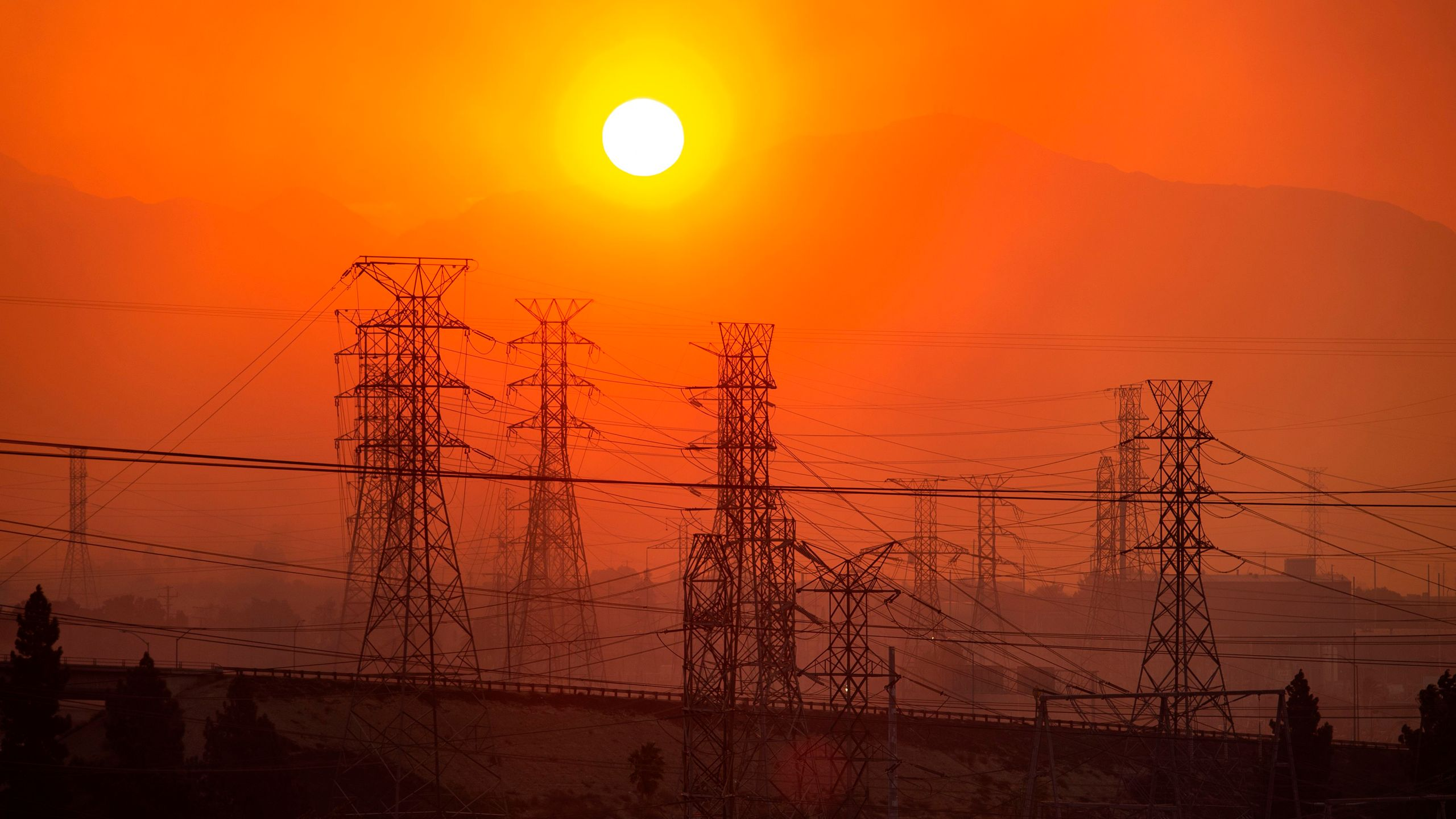 The sun rises over power lines along a smokey horizon during the Saddleridge Fire in Newhall on Oct. 11, 2019. (Credit: Josh Edelson/AFP via Getty Images)