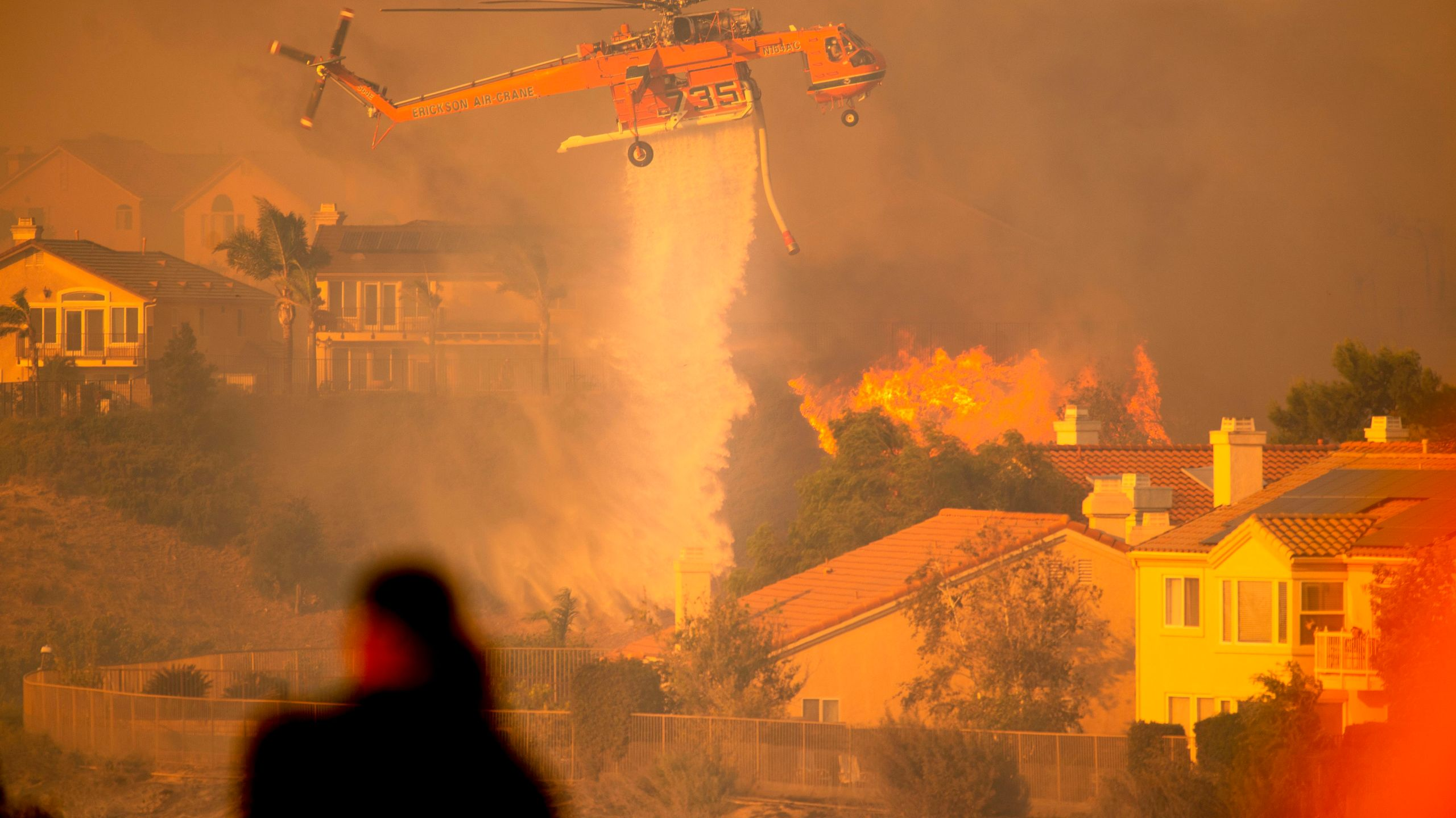 A helicopter drops water to help fight flames as the Saddleridge Fire moves through Porter Ranch on Oct. 11, 2019. (Credit: Josh Edelson / AFP/ Getty Images)