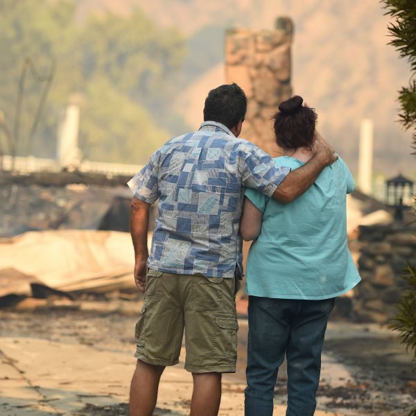 Eyad Jarjour, left, consoles his neighbor as she views her burned home after flames from the Saddleridge Fire tore through Granada Hills on Oct. 11, 2019. (Credit: Josh Edelson / AFP / Getty Images)