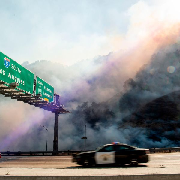 A police car passes by a flaming hillside during the Saddleridge fire in Newhall, California on Oct. 11, 2019. (Credit: Josh Edelson/AFP via Getty Images).