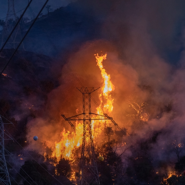 Flames heat up high power lines at the Saddleridge Fire on Oct. 11, 2019, near Newhall. (Credit: David McNew/Getty Images)