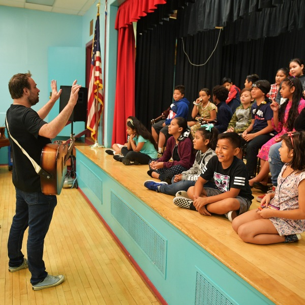 Phil Barton and fifth graders practice onstage during the Country Music Hall of Fame and Museum Brings Words and Music Program at Elysian Heights Elementary School on Sept. 16, 2019, in Los Angeles. (Credit: Matt Winkelmeyer/Getty Images for Country Music Hall of Fame and Museum)