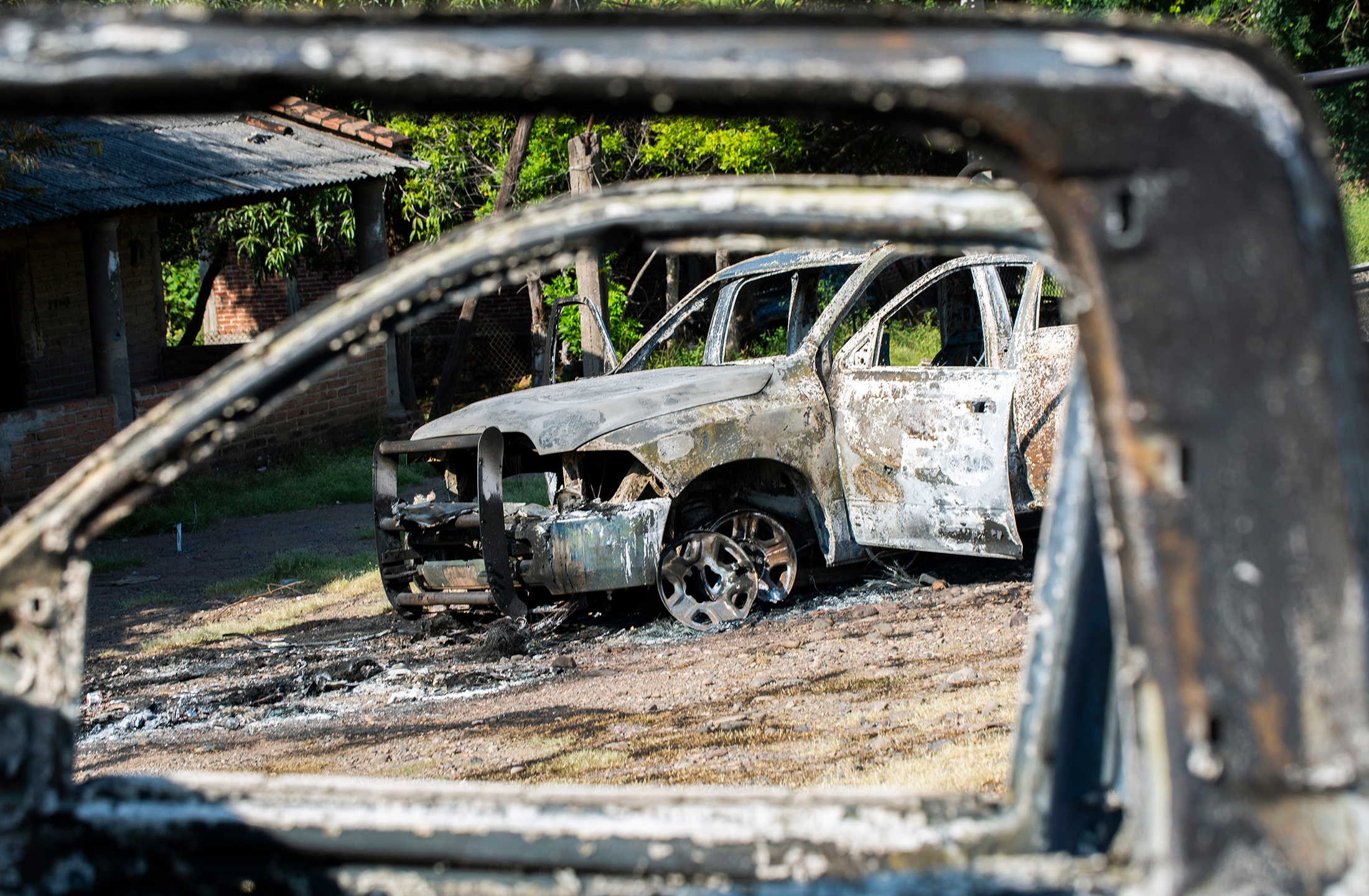 Police vehicles are seen after being torched by gunmen who also killed 14 officers in an ambush in the community of Aguililla, in the Mexican state of Michoacan, on Oct. 14, 2019. (Credit: Enrique Castro / AFP / Getty Images)
