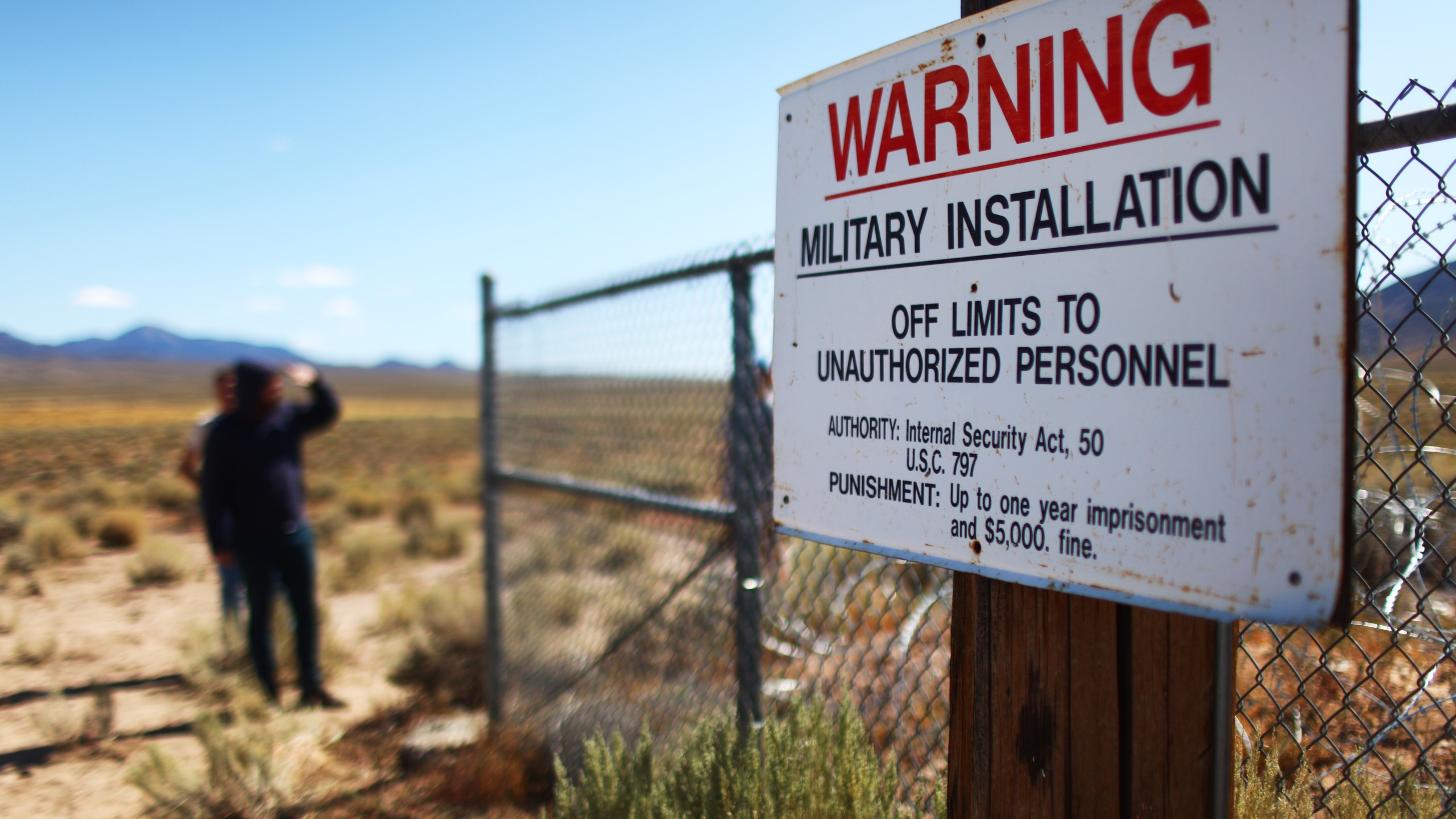 People gather at an entrance gate to the Nevada Test and Training Range, the official name for the facility containing what is known as Area 51, near Rachel, Nevada, on Sept. 20, 2019. (Credit: Mario Tama / Getty Images)