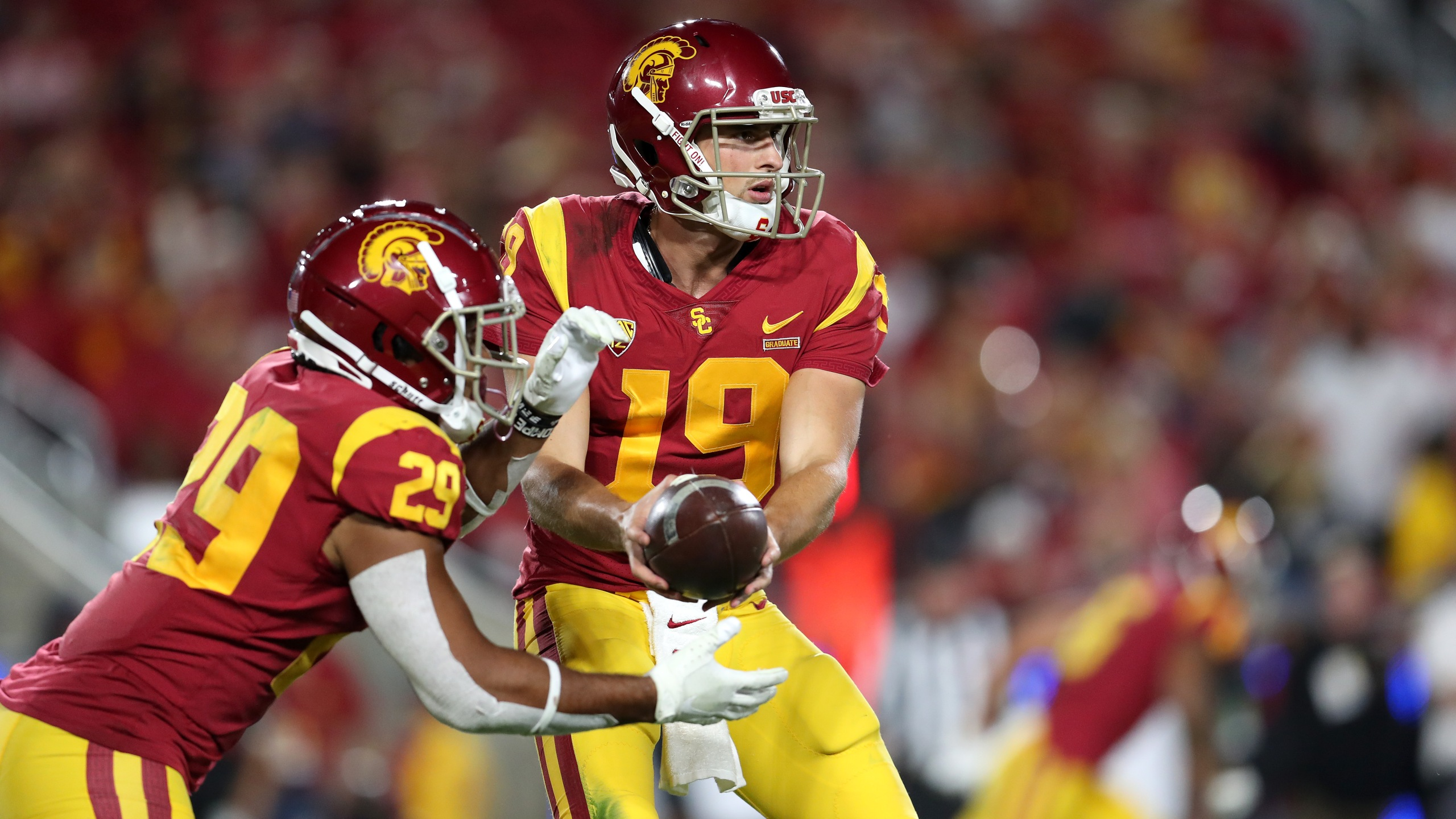 Matt Fink, No. 19, of the USC Trojans hands off to teammate Vavae Malepeai, No. 29, during a match against the Utah Utes at Los Angeles Memorial Coliseum on Sept. 20, 2019. (Credit: Meg Oliphant/Getty Images)