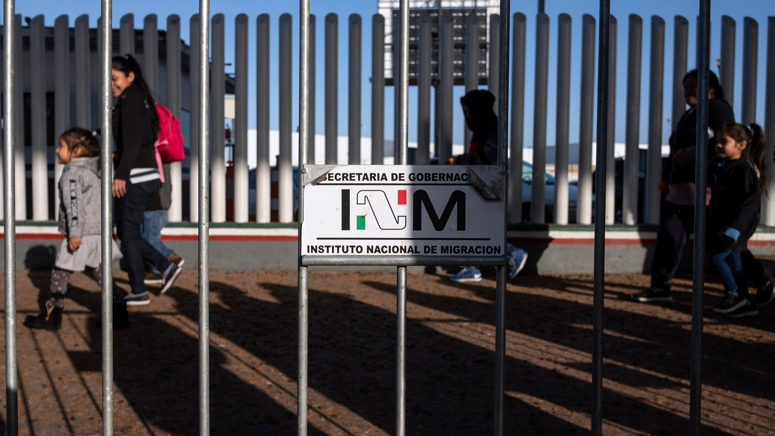 Asylum seekers walk for their appointment date with U.S. authorities outside El Chaparral crossing port on the US-Mexico border in Tijuana, Baja California state, Mexico, on Oct. 18, 2019. (Credit: GUILLERMO ARIAS/AFP via Getty Images)