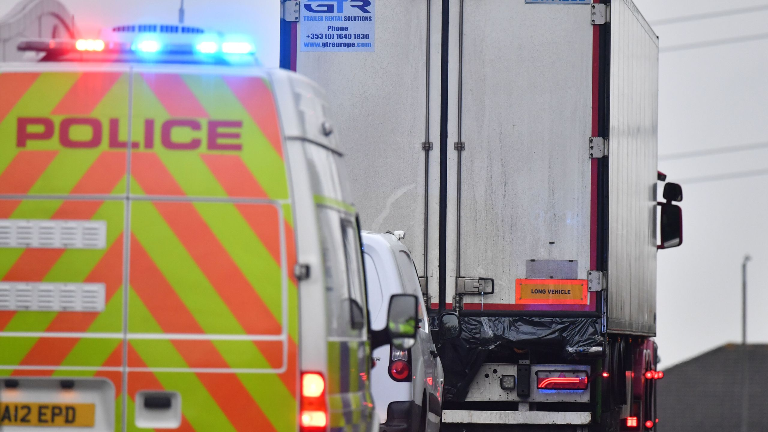 Police officers drive away a lorry, with black plastic visible at the rear, in which 39 dead bodies were discovered. It sparked a murder investigation at Waterglade Industrial Park in Grays, east of London, on Oct. 23, 2019.(Credit: BEN STANSALL/AFP via Getty Images)