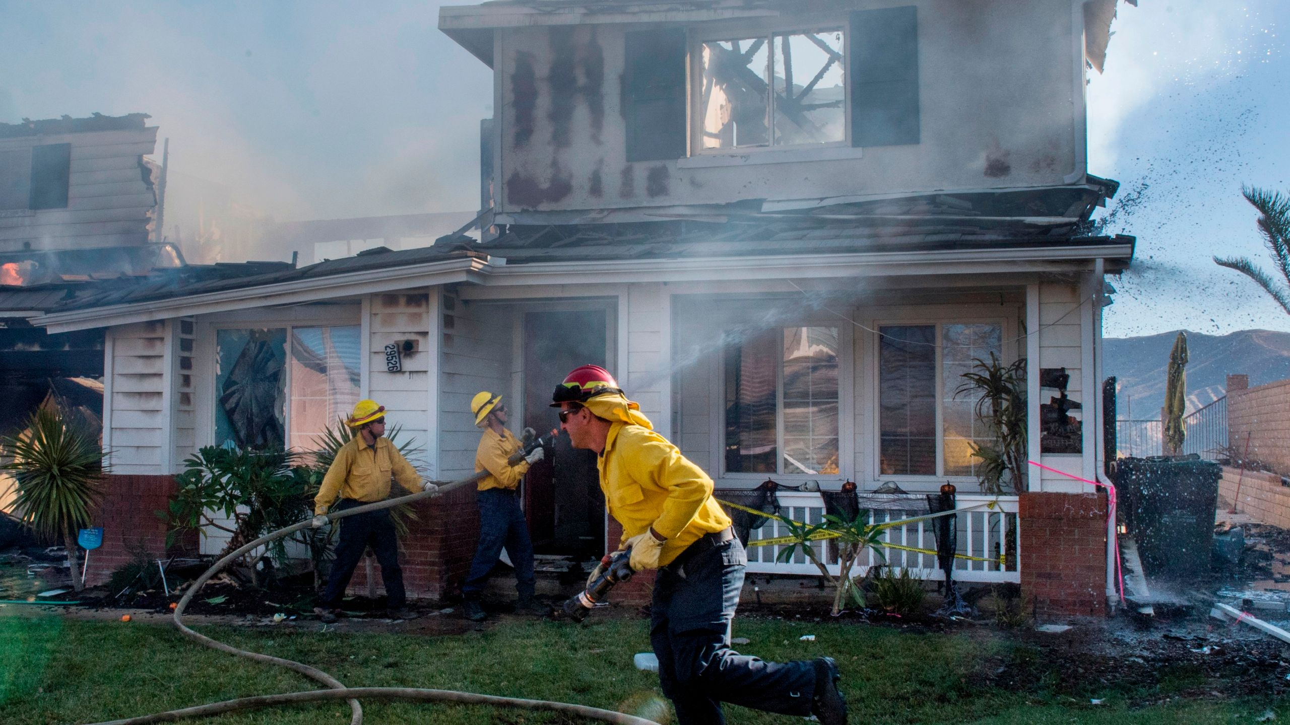 Firefighters hose down a burning house during the Tick Fire in Agua Dulce near Santa Clarita, California on Oct. 25, 2019. (Credit: MARK RALSTON/AFP via Getty Images)