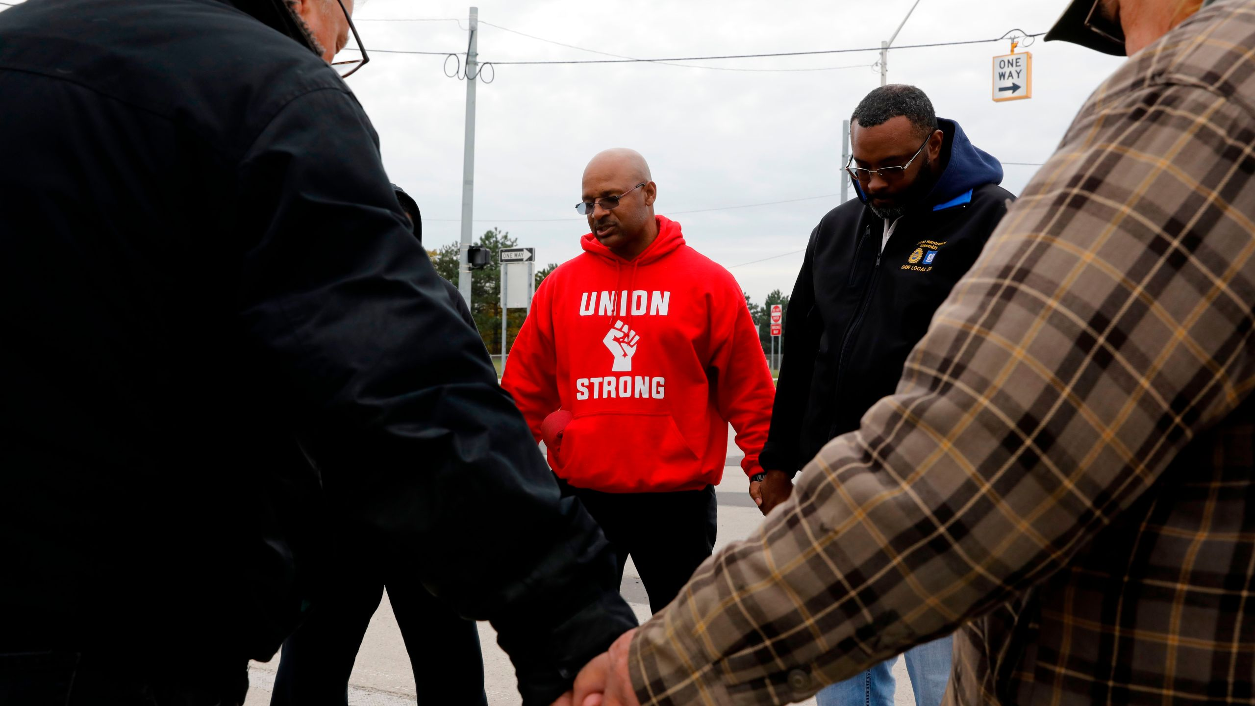 United Auto Workers member Joe Ryan, center, leads a prayer circle to recite a strike closing prayer outside of the General Motors Detroit-Hamtramck Assembly plant in Detroit, Michigan, on Oct. 25, 2019. (Credit: Jeff Kowalsky / AFP / Getty Images)