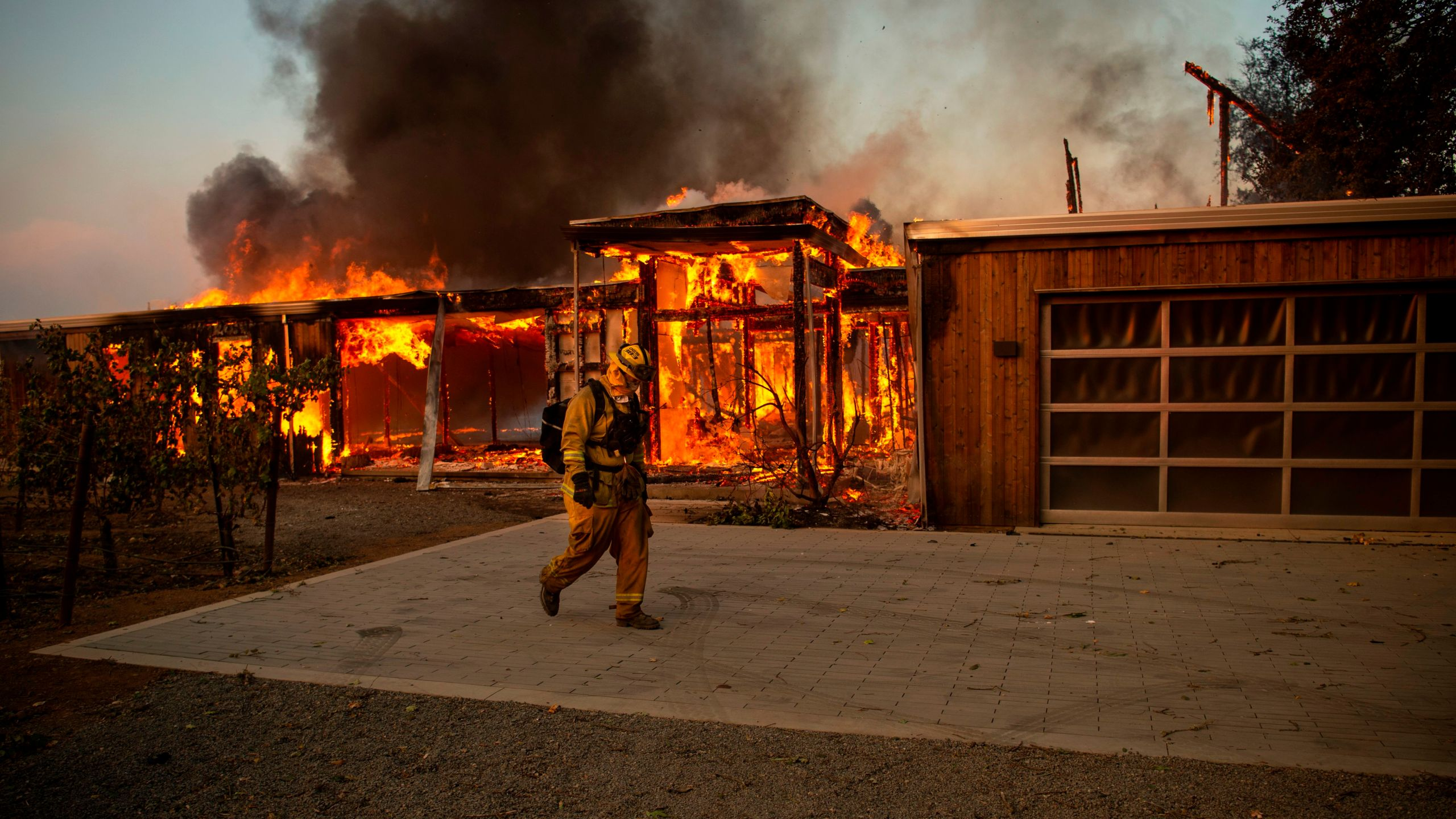 A firefighter walks by a house as it burns during the Kincade fire in Healdsburg, Calif. on Oct. 27, 2019. (Credit: JOSH EDELSON/AFP via Getty Images)