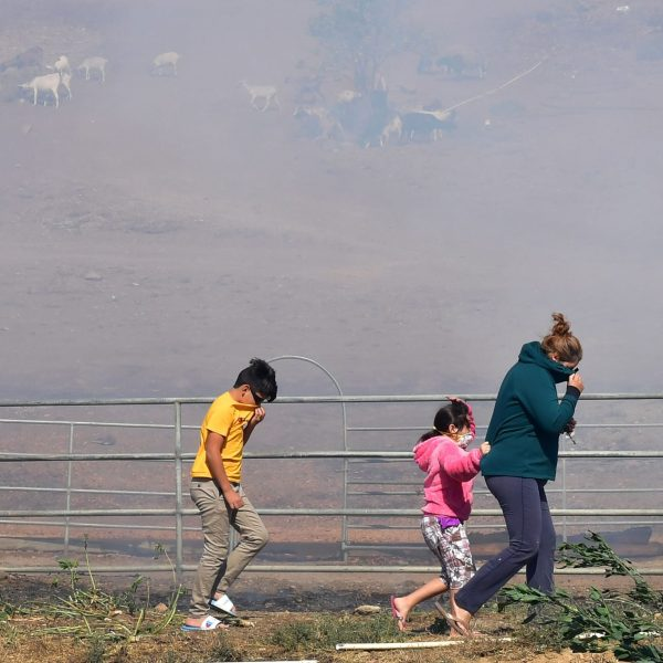 A woman and children brace themselves from strong winds and smoke near the Ronald Reagan Presidential Library in Simi Valley during the Easy Fire. (Credit: FREDERIC J. BROWN/AFP via Getty Images)