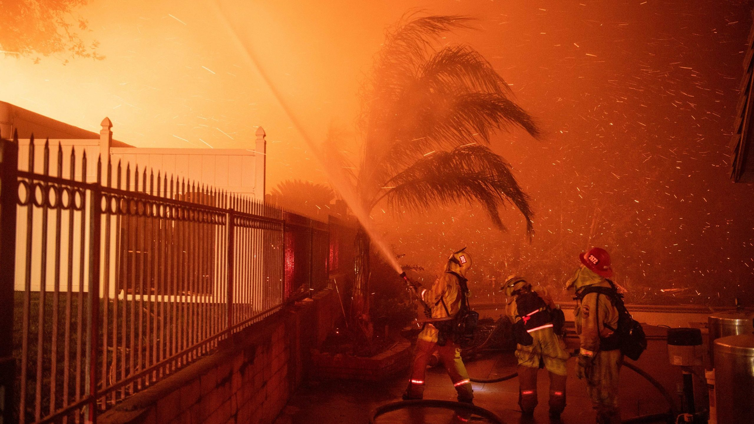 Firefighters battle wind-whipped flames engulfing multiple homes during the Hillside Fire in the North Park neighborhood of San Bernardino on Oct. 31, 2019. (Credit: Josh Edelson / AFP / Getty Images)
