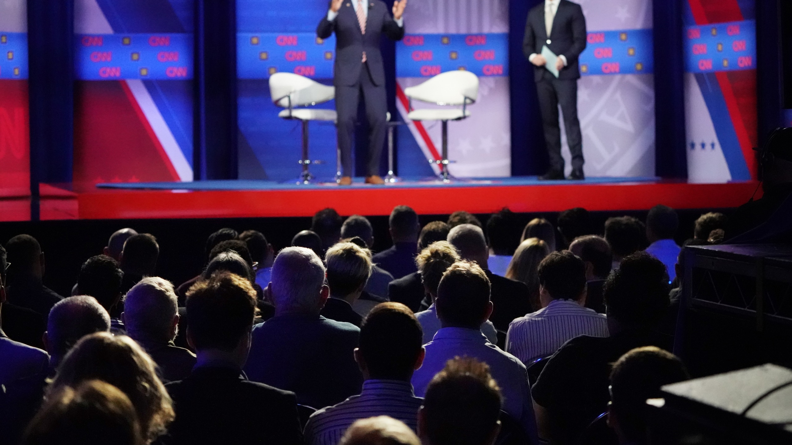 Audience members watch as Democratic presidential candidate and former Vice President Joe Biden speaks, as CNN moderator Anderson Cooper looks on, at the Human Rights Campaign Foundation and CNN's presidential town hall focused on LGBTQ issues in Los Angeles on Oct. 10, 2019. (Credit: Mario Tama / Getty Images)