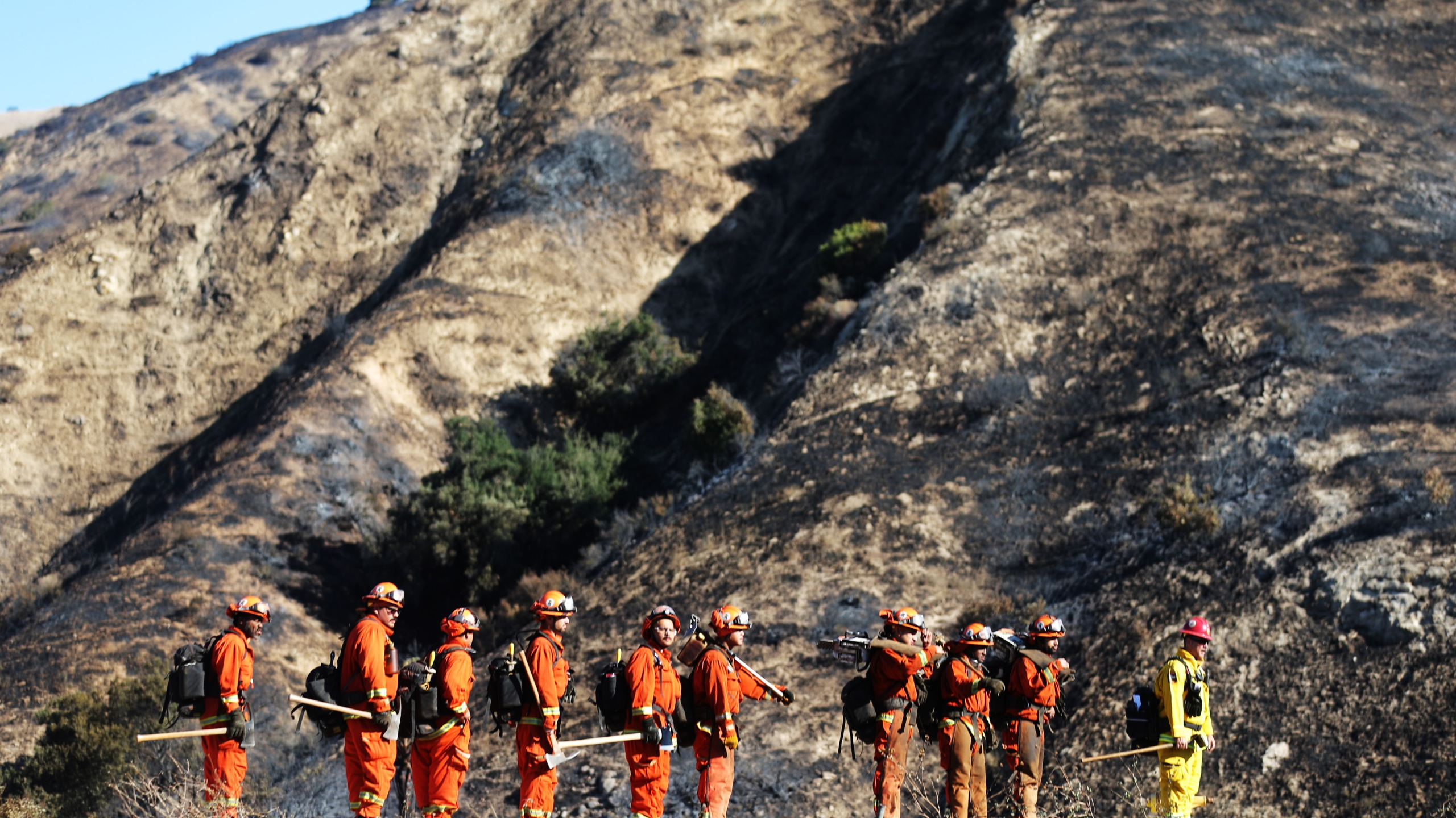 An inmate firefighter crew from Prado Conservation Camp, led by a fire captain (R), prepare to put out hot spots from the Saddleridge Fire on Oct. 12, 2019, in Porter Ranch, California. (Credit: Mario Tama/Getty Images)