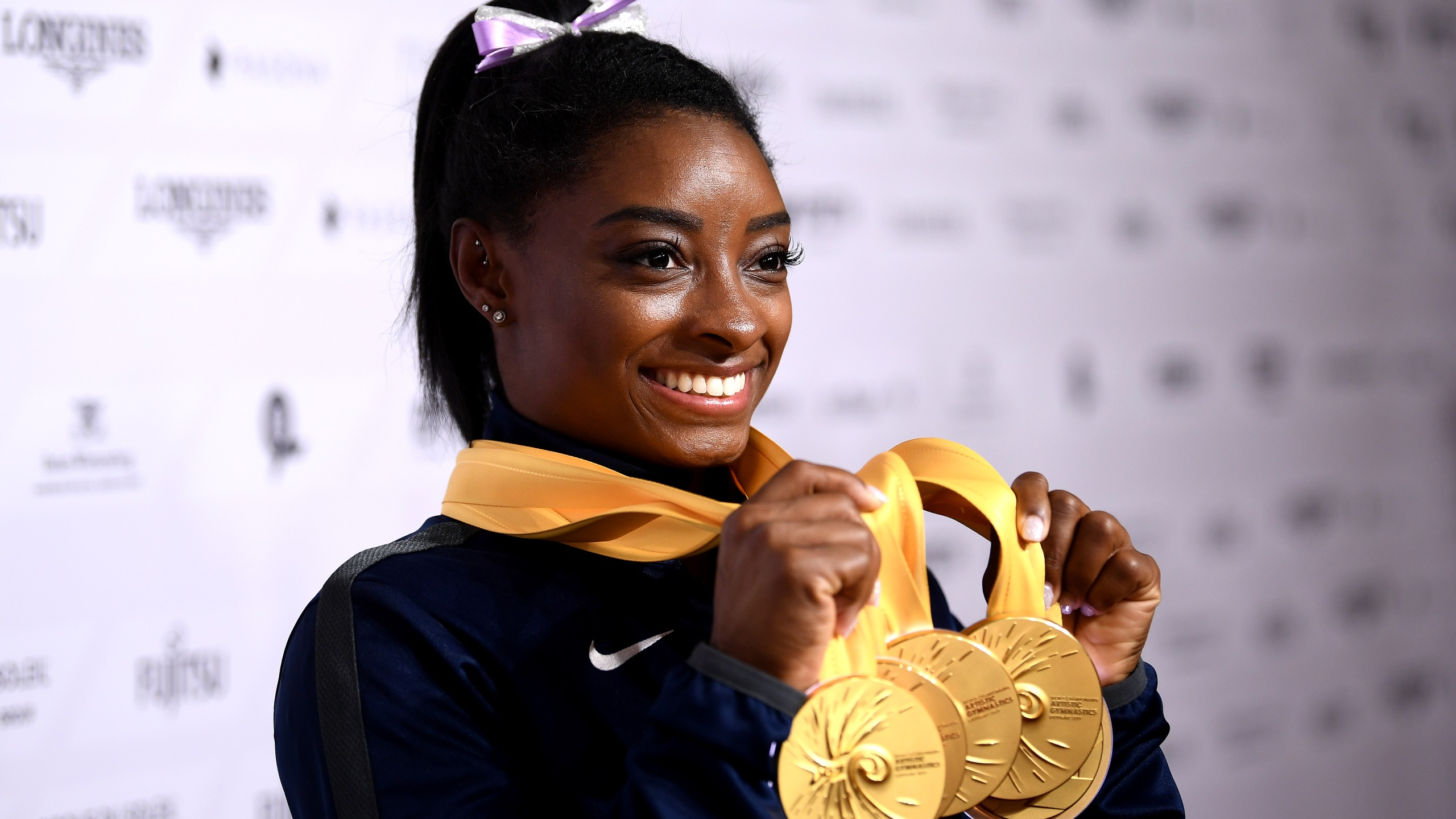 Simone Biles poses for photos with her multiple gold medals during day 10 of the 49th FIG Artistic Gymnastics World Championships on Oct. 13, 2019, in Stuttgart, Germany. (Credit: Laurence Griffiths/Getty Images)