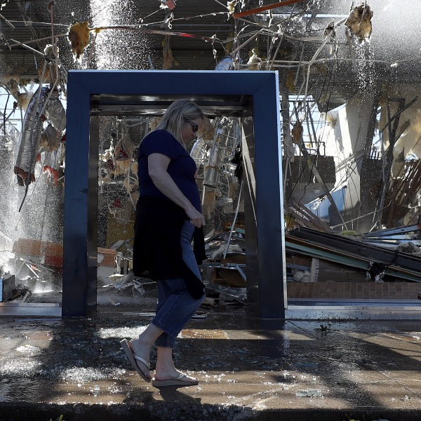 Stephanie Watson of Dallas walks in front of a damaged Talbot's store in Dallas on Oct. 21, 2019. (Credit: Ronald Martinez / Getty Images)