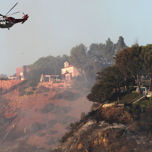A firefighting helicopter flies near homes during the Palisades Fire in Pacific Palisades on Oct. 21, 2019. (Credit: Mario Tama / Getty Images)