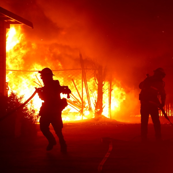 Firefighters battle the Kincade Fire as it burns a barn on Oct. 27, 2019, in Santa Rosa, Calif. (Credit: Justin Sullivan/Getty Images)
