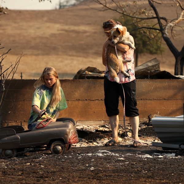 A family walks through a home that was destroyed by the Kincade Fire on Oct. 28, 2019 in Calistoga, California. (Credit: Justin Sullivan/Getty Images)