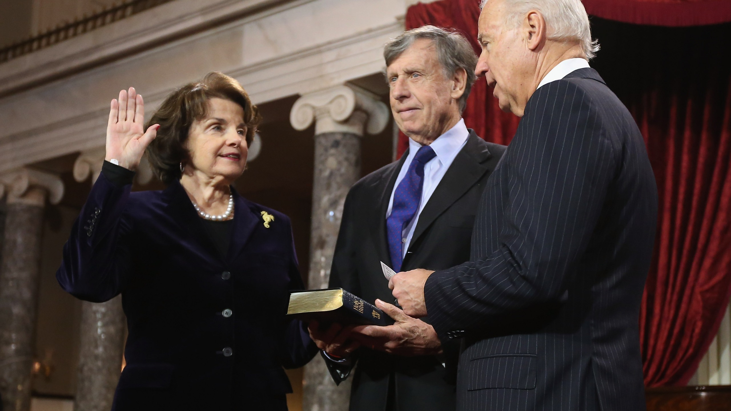 Sen. Dianne Feinstein participates in a reenacted swearing-in with her husband Richard C. Blum and U.S. Vice President Joe Biden in the Old Senate Chamber at the U.S. Capitol on Jan. 3, 2013. (Credit: Chip Somodevilla/Getty Images)
