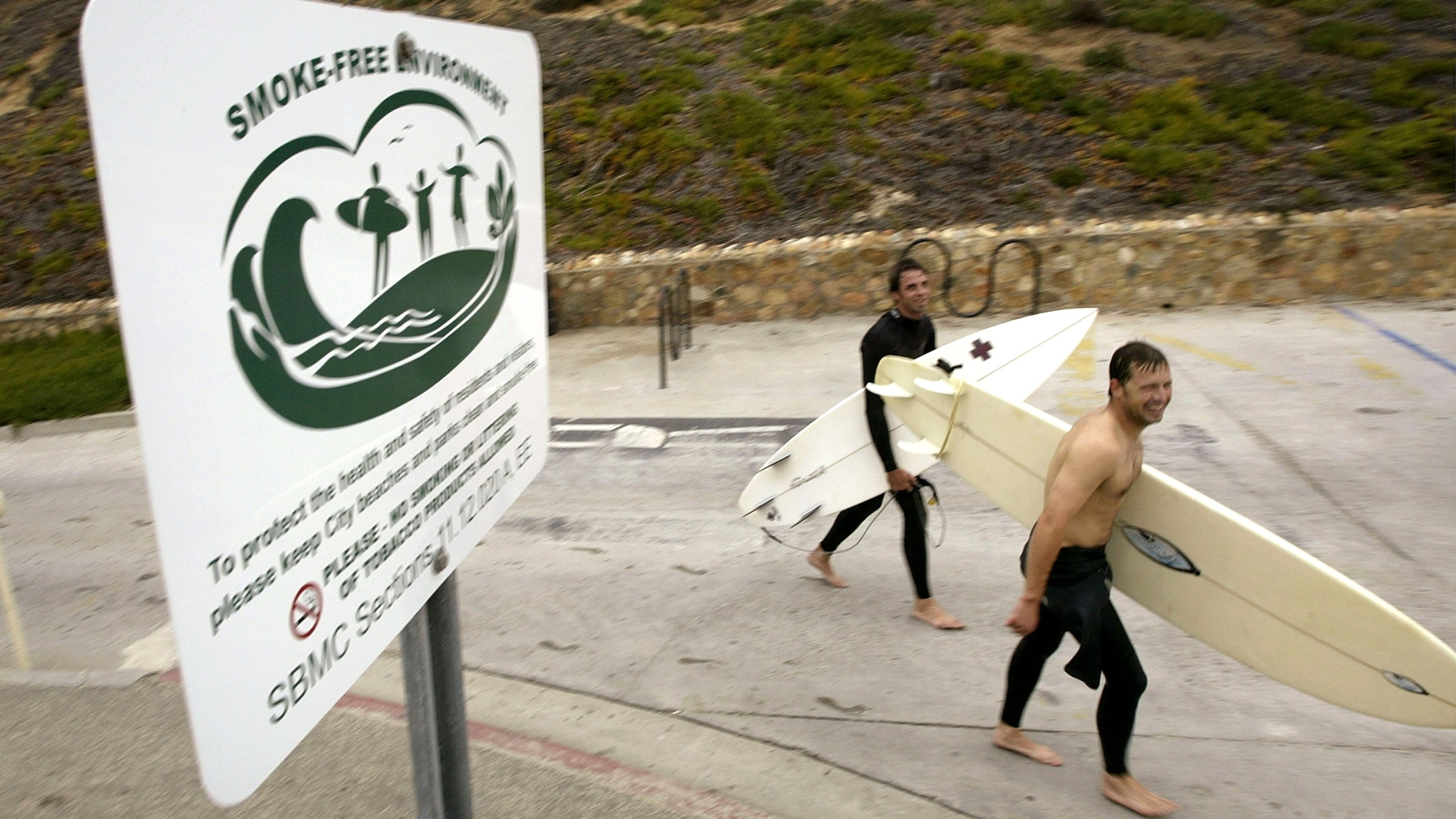 A surfer walks past a no smoking sign on March 22, 2004 in Solana Beach. (Credit: David McNew/Getty Images)