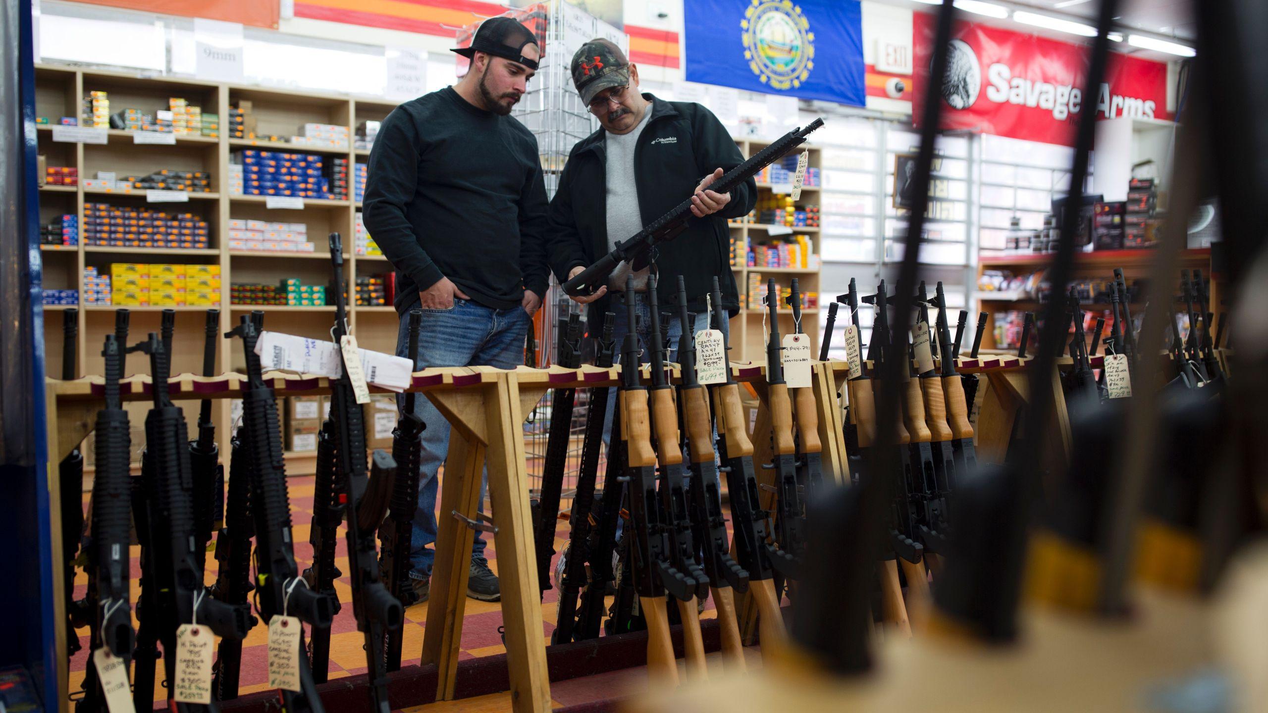 Customers look at a long gun at a gun shop on Nov. 5, 2016, in Merrimack, New Hamp. (Credit: DOMINICK REUTER/AFP/Getty Images)