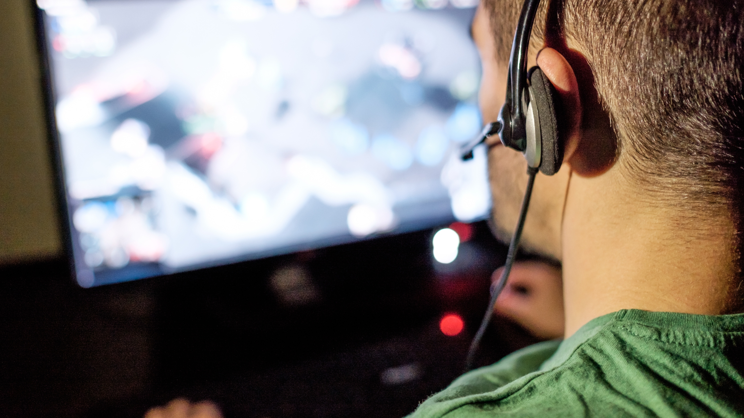 A man with headphones is seen playing video game in this file photo. (Credit: iStock / Getty Images Plus)