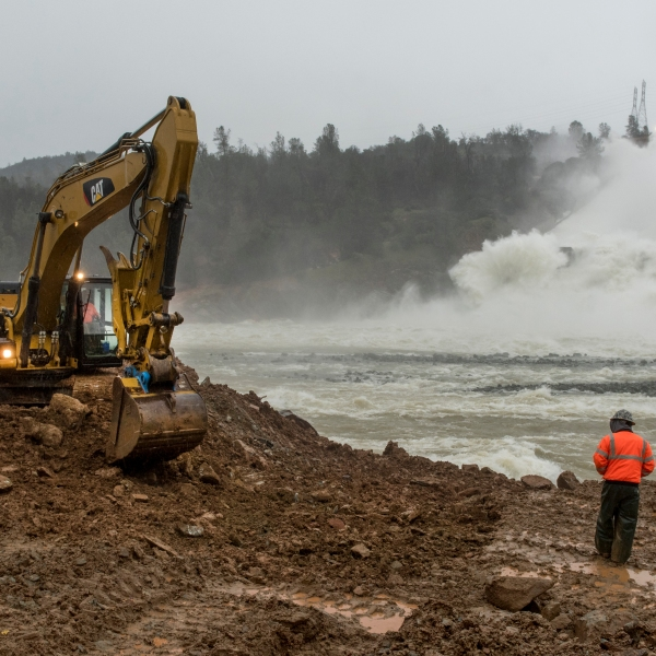Work continues along the riverbank across the damaged spillway at Oroville Dam on Feb. 17, 2017, in Oroville, California. (Credit: Brian Baer/ California Department of Water Resources via Getty Images)