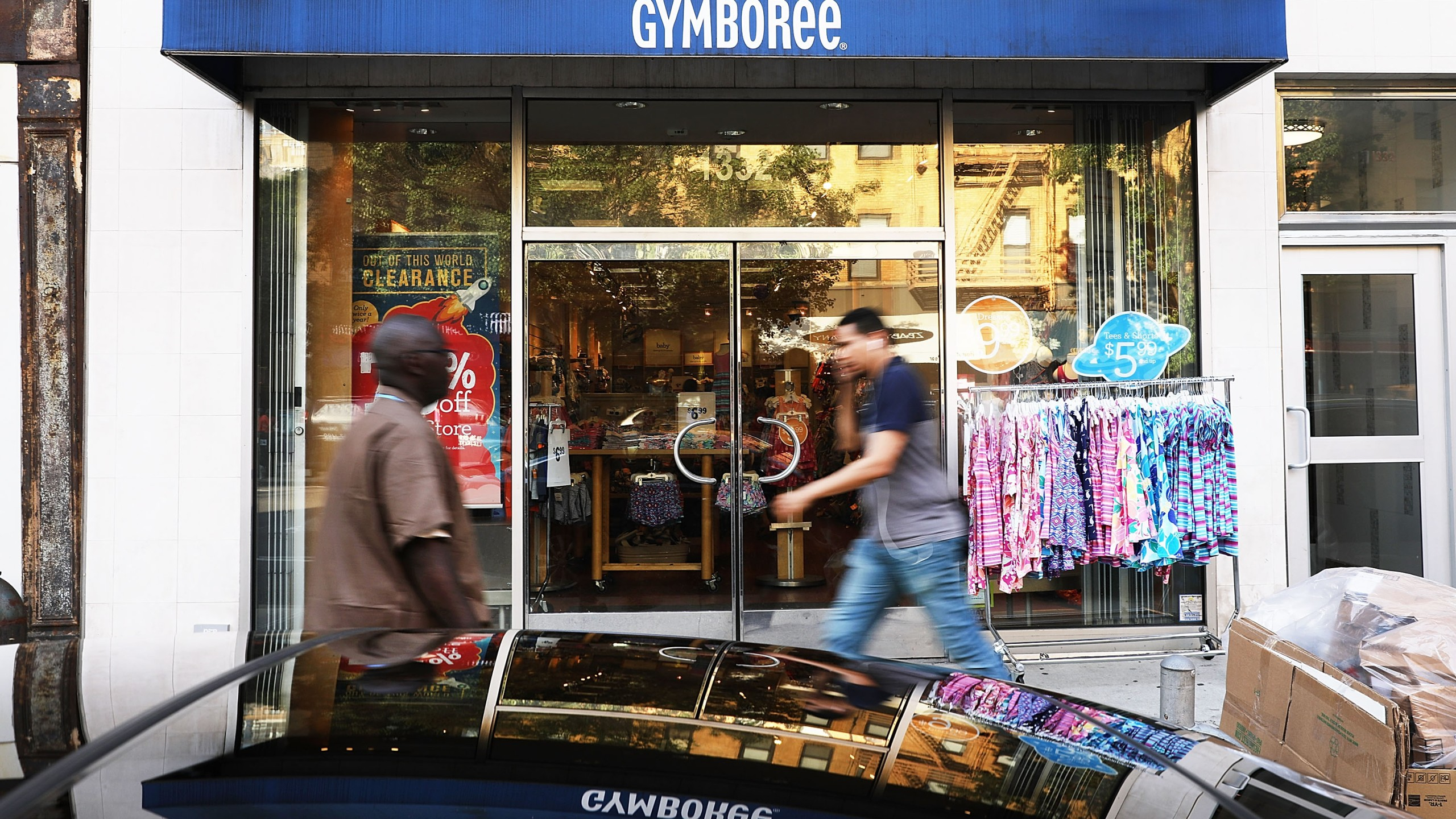 People walk by the children's clothing retailer Gymboree, which has filed for bankruptcy protection on June 13, 2017 in New York City. (Credit: Spencer Platt/Getty Images)