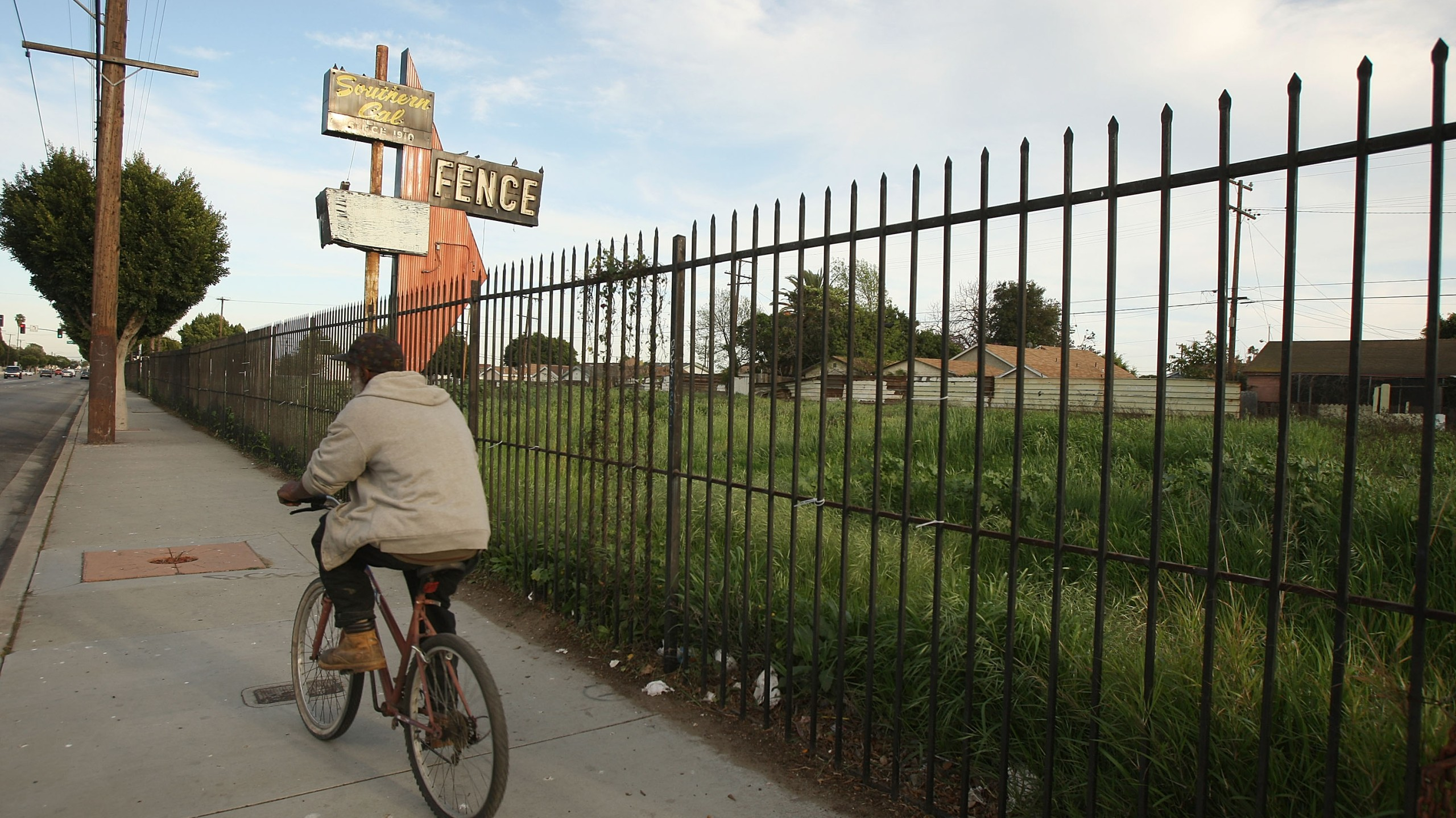 A man bicycles past a lot in Compton vacated years ago when a long-established business failed, on March 3, 2009. (Credit: David McNew / Getty Images)