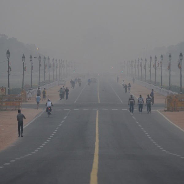 People walk early in the morning as smogs covers Rajpath ceremonial boulevard near India Gate war memorial in New Delhi on November 6, 2017. (Credit: SAJJAD HUSSAIN/AFP/Getty Images)