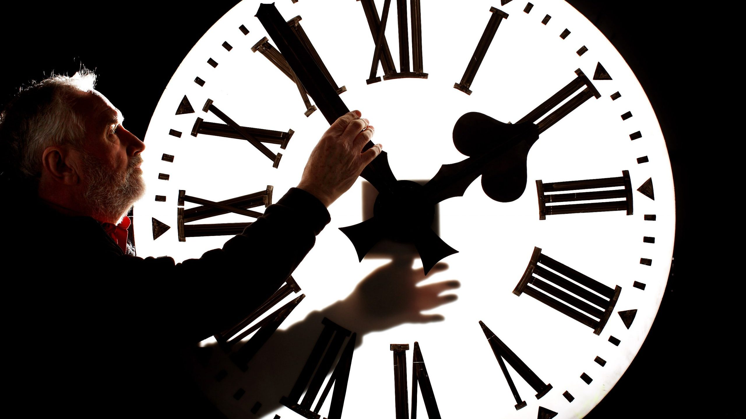 A man adjusts a clock on March 26, 2010, in Edinburgh, Scotland. (Credit: Jeff J Mitchell/Getty Images)