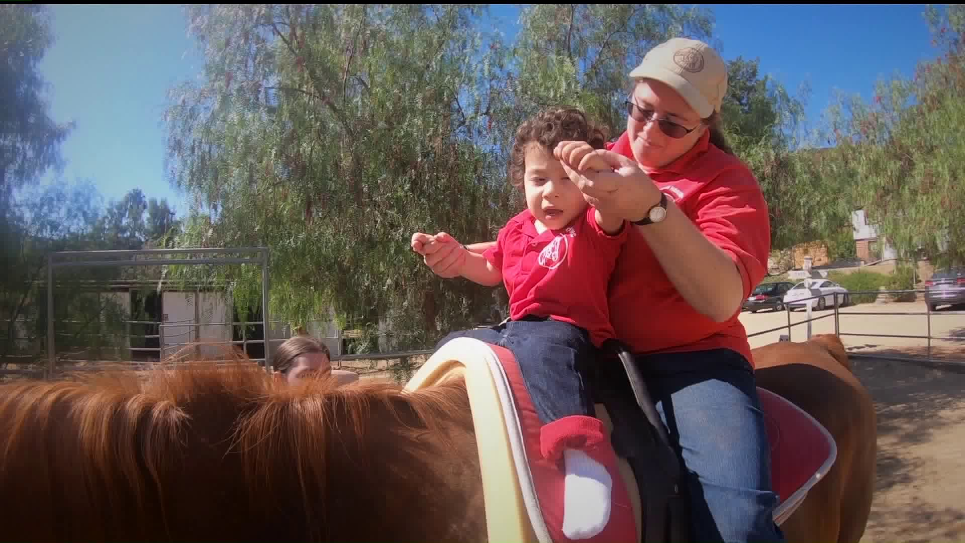A young patient receives equine therapy at Ahead with Horses in Shadow Hills on Oct. 3, 2019. (Credit: KTLA)