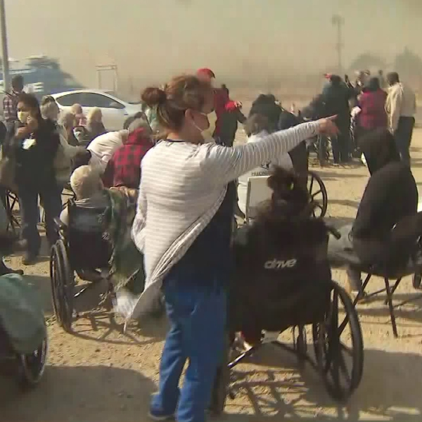 Residents of an evacuated skilled nursing facility, many in wheelchairs, could be seen awaiting transportation to hospitals in the Hill Fire in Jurupa Valley on Oct. 30, 2019. (Credit: KTLA)