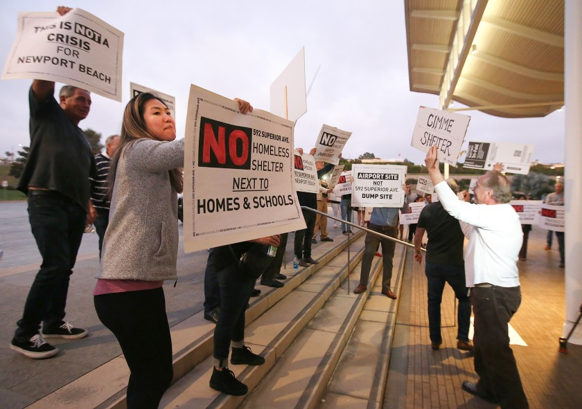 Protesters who are against a possible homeless shelter at the Newport Beach public works yard on Superior Avenue picket outside City Hall before a City Council meeting on Oct. 8, 2019. (Credit: Don Leach / Daily Pilot via Los Angeles Times)